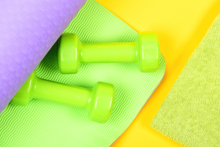 Dumbbells on green and purple yoga mat and towel isolated on yellow background, top view. Sports concept Reklamní fotografie