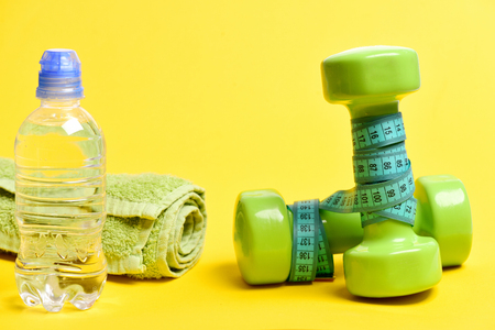 Water bottle, green lightweight dumbbells, cyan blue measuring tape and soft bath towel, isolated on yellow. Concept of sportive day Stock Photo