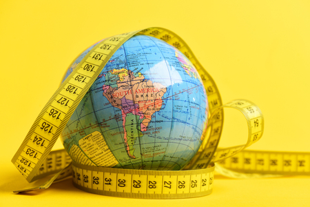 Earth globe wrapped around with measuring tape isolated on bright yellow background. Symbol of worldwide food issue