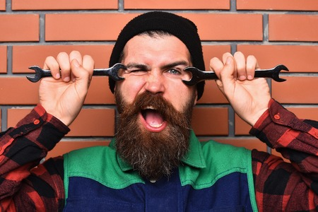 funny bearded man: Bearded man, long beard. Brutal caucasian happy funny mechanic, unshaven hipster in black hat, checkered shirt and uniform holding wrenches on brick wall studio background. People on work concept Stock Photo