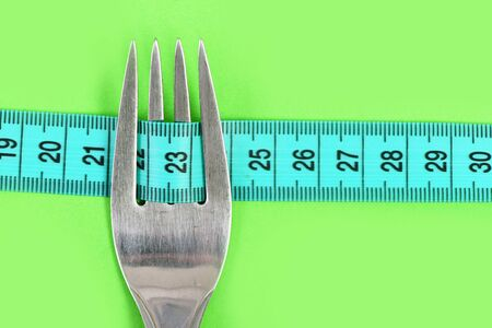 Tape for measuring focused on number twenty three held inside metal fork tines isolated on green background, close up and copy space. Concept of diet and nutrition