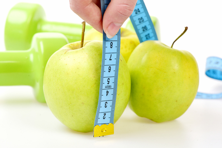 Apples measured by cyan flexible ruler in fingers, green dumbbells lying behind, isolated on white background, defocused. Close up, concept of healthy nutrition Stock Photo
