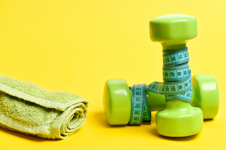 Dumbbells with cyan measuring tape and green towel near them, copy space. Day at gym and healthy lifestyle concept Stock Photo