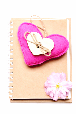 information age: Heart and notebook. Big pink felt heart with wooden decoration and sakura flower lying on beige notepad cover isolated on white background. Diary and teen age