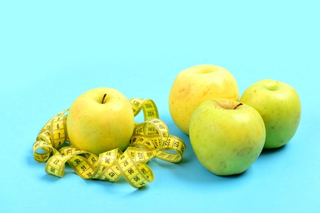 millimeter: Apples in green color and yellow tape for measuring isolated on light blue background. Symbol of eco food and diet