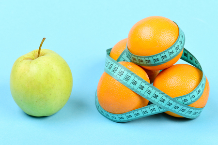 Apple near pile of oranges wrapped around with cyan tape for measuring, isolated on turquoise background. Symbol of vitamin diet, slim shape and healthy food