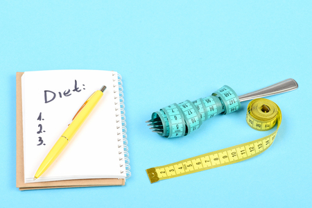 Tape for measuring in yellow colour and cyan blue one wrapped around fork near notebook with diet checklist and yellow pen on it, isolated on light blue background Stock Photo