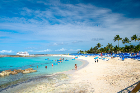 Great stirrup cay, Bahamas - January 8, 2016: people resting on beach on white sand with turquoise sea or ocean and lounge chairs on sunny day on blue sky. Summer vacation. Tropical resort. Paradise