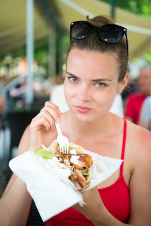 beefburger: pretty girl or Woman eating sandwich gyros. Girl with pleasure eats burger after diet. She opened her mouth, holding a gyros on his outstretched hands and closed her eyes.