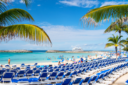 Great stirrup cay, Bahamas - January 8, 2016: rows of blue lounge chairs on sea beach with white sand, green palms, people and cruise ship on idyllic skyline. Summer vacation and resort. Paradise