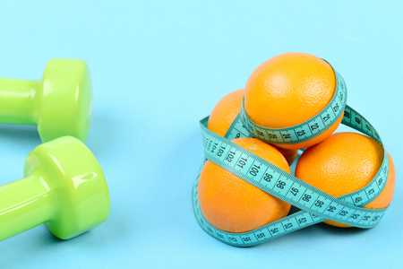 Pair of dumbbells next to oranges wrapped around with cyan measuring tape, isolated on turquoise background. Healthy nutrition and fitness concept Stock Photo