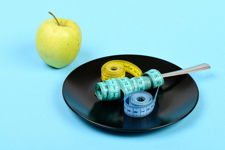 Apple in green color next to black plate with measuring tapes and fork on it, isolated on light blue background Stock Photo