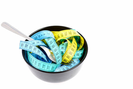 Bowl of flexible rulers in yellow, cyan and blue with metal cutlery isolated on white background, copy space. Concept of healthy lifestyle and nourishment Stock Photo