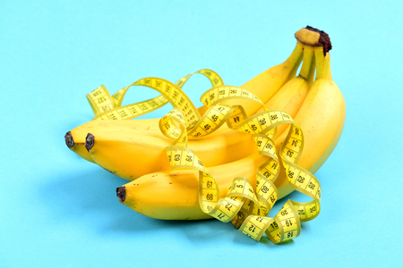 millimeter: Bunch of bananas and curled yellow measuring tape on it, isolated on light blue background. Concept of vitamins and diet Stock Photo
