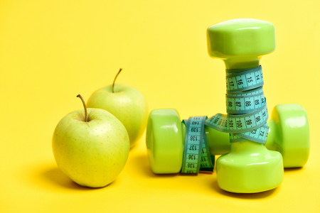Pair of fresh apples near green dumbbells wrapped with turquoise measure tape isolated on yellow background. Concept of healhy food and workout