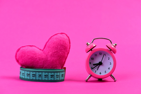 Roll of greenish blue measuring tape around heart next to alarm clock, isolated on magenta pink background with copy space