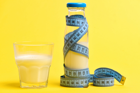 Tape for measurement in blue color twisted around milk in bottle and glass, isolated on yellow background. Concept of healthy diet and lifestyle