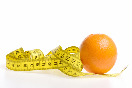 millimeter: Knot of measuring tape in yellow colour lying near orange fruit, isolated on white background with copy space. Vegetarian food and slim body concept