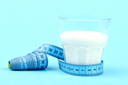 Tape for measuring ties around glass of milk, isolated on light blue background. Concept of vitamin diet and calcium nutrition