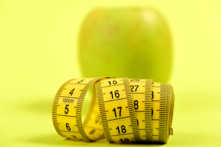 Tape for measurement in yellow colour with green apple behind, on light yellow background, close up and selective focus. Concept of dieting, slim shape and healthy nutrition