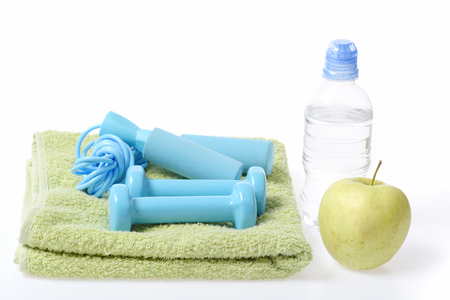 Gym time: cyan blue barbells and tied skipping rope on green towel, fresh apple and water bottle isolated on white background. Sports, fitness and diet concept Stock Photo
