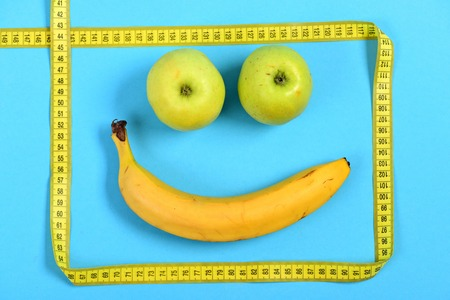 smiley pouce: Tape for measurement making yellow frame with banana and apple inside: happy smiling face isolated on blue background. Happiness and joy expression concept