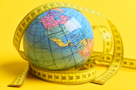 globe with measuring tape on yellow background. Diet and health in world concept Stock Photo