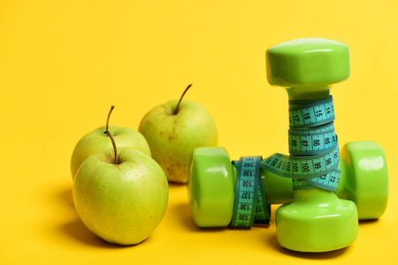Dumbbells in green color wrapped around with cyan blue measuring tape near greenish yellow apples isolated on yellow background. Concept of sports and regime