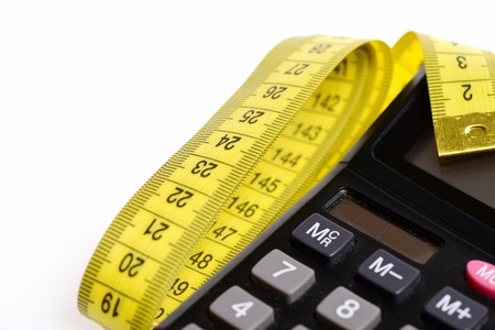 Calculator and yellow measuring tape isolated on white background, defocused parts. Concept of counting calories