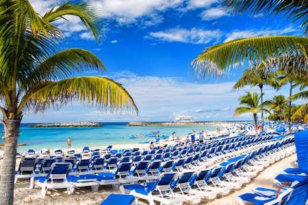 Great stirrup cay, Bahamas - January 8, 2016: rows of blue lounge chairs on sunny beach with white sand, green palms, people and cruise ship in blue sea on idyllic skyline. Summer vacation in paradise Stock Photo