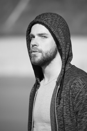 young people and emotions concept, serious hooded man or boy with beard sunny outdoor on blurred background, black and white