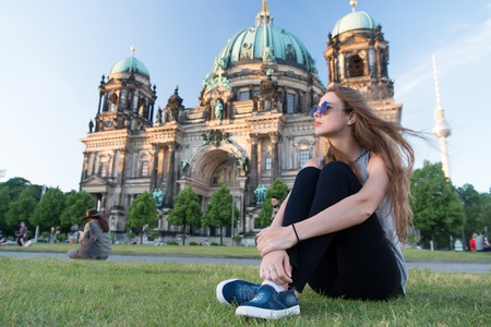 Pretty gil sitting in front of Berlin Cathedral at beautiful sunset wearing sunglasses, relax and enjoy life