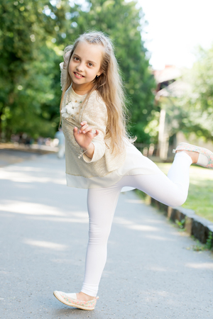 Cute little girl dancing at the street at summer day Stock Photo