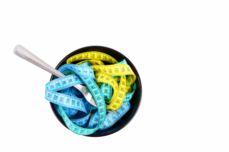 Composition of measuring tapes in different colors put in dark bowl with fork isolated on white background, top view and copy space. Healthy lifestyle concept