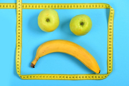 Face made of fruit with sad expression: banana and apples making mouth and eyes framed with yellow flexible ruler, isolated on cyan blue background. Concept of food art and minimalism