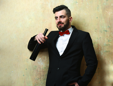 suite: Man smiling and holding with bottle of wine in suit with red bow on background of beige color wall. Concept of party time and rest