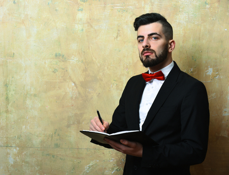 Bearded employer with cunning face expression and neat stylish outfit writes notes in his planner, cracked vintage beige background with copy space. Concept of planning and time management Stock Photo