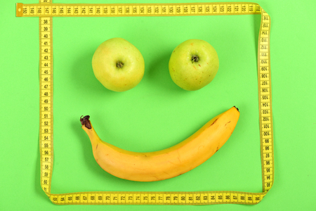 Fruit face composition. Happy smiley made of apples, banana and yellow sewing centimeter, isolated on green background. Concept of happiness and food art Stock Photo