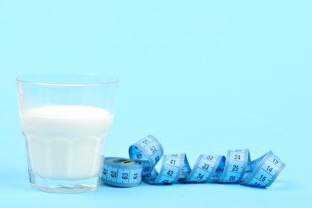 Glass of milk next to untwisted roll of blue measuring tape, isolated on turquoise background with copy space