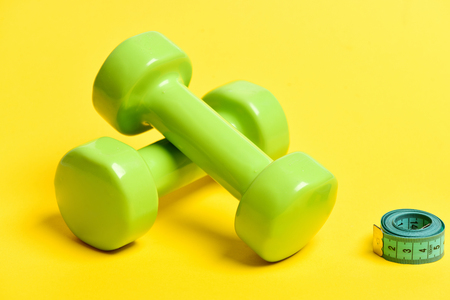 Tape for measuring in turquoise roll near pair of green dumbbells crossed and isolated on yellow background. Concept of shape measurement and sports Stock Photo