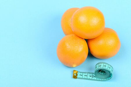 Roll of cyan measuring tape next to oranges, isolated on light blue background with copy space. Concept of fruit diet, vitamin nutrition and weight management