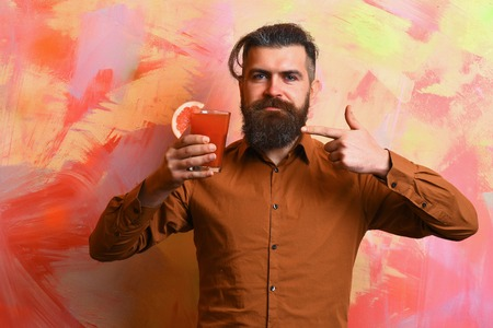 Bearded man, long beard. Brutal caucasian smiling hipster with moustache in brown shirt holding tropical alcoholic fresh cocktail with orange piece on colorful texture background Stock Photo