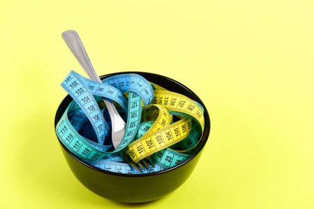 Tapes for measuring in different colors mixed in dark bowl with fork isolated on light yellow background. Concept of proper nutrition and regime