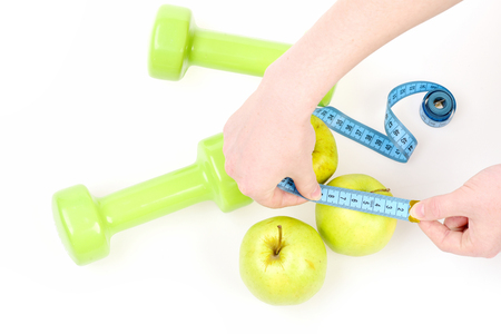 Hands holding cyan flexible ruler and measuring apple with another apple fruit and green lightweight dumbbells, isolated on white background. Concept of sports, healthy nutrition and fresh food diet