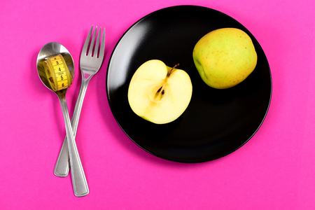 Bright composition of vegetarian food: apple halves and whole fruit, traditional cutlery and rolled tape in hands isolated on pink background Stock Photo