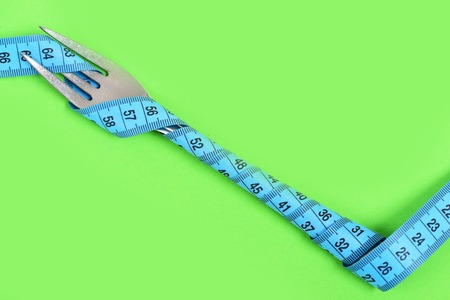 Cutlery diet composition. Fork in silver colour made of metal wrapped with cyan blue measuring ruler isolated on green background, copy space. Concept of healthy shape and food