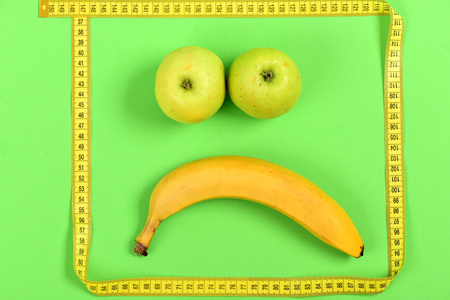 smiley pouce: Sad fruit face. Smiley with disappointed expression made of banana and apples with measuring tape in yellow color isolated on light green background. Concept of emotions and healthy food