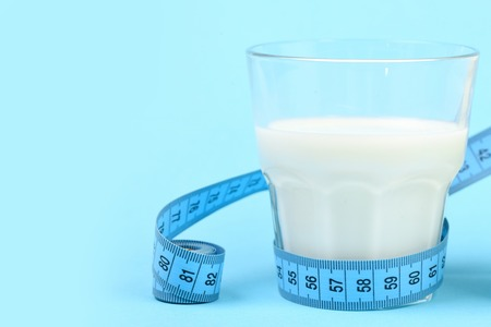 Glass filled with milk and tied around with measuring tape, isolated on light blue background with copy space