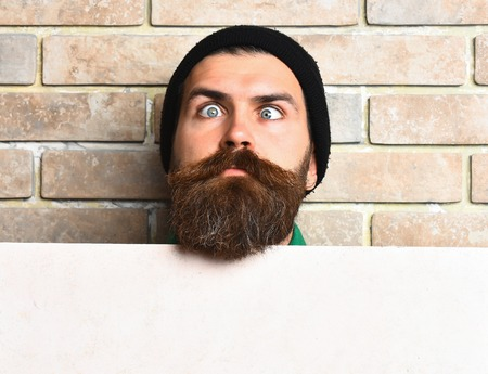 Bearded man, long beard. Brutal caucasian unshaven hipster in black hat have crazy eyes with strabismus holding white paper sheet on beige brick wall studio background, copy space Stock Photo