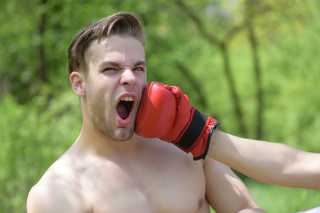 Man punched in face with boxing glove on green trees background. Concept of sports and fight